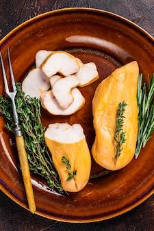 Pierś z kurczaka wędzona na gorąco mięso drobiowe w rustykalnym talerzu z ziołami. ciemne tło. widok z góry.