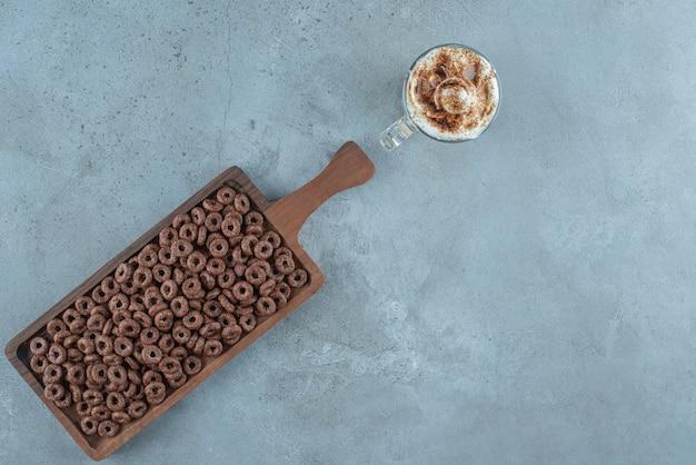 Pierścień kukurydziany w desce obok szklanki kawy mlecznej, na niebieskim tle.
