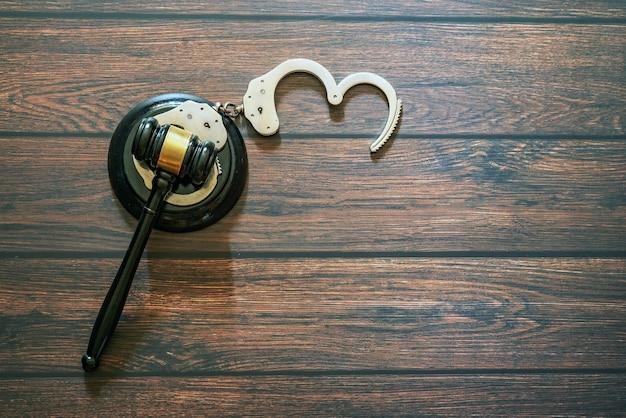 Pierścień sędziowski z kajdankami na drewnianym stole