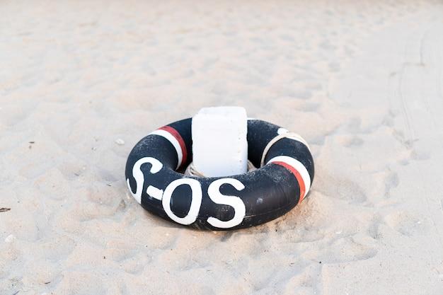 Pierścień życia przygotowany na plaży z bliska. pierścień ratunkowy sos. pierścień ratunkowy przygotowany do pomocy ludziom po wypadku z powodu małżeństwa.