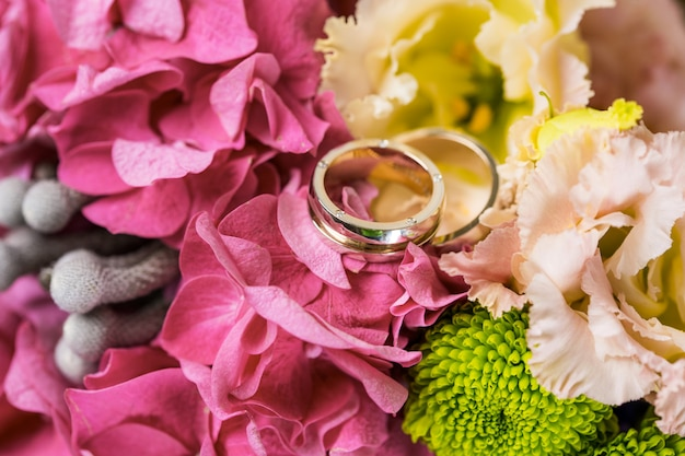 Pierścienie nowożeńców w bukiecie kwiatów