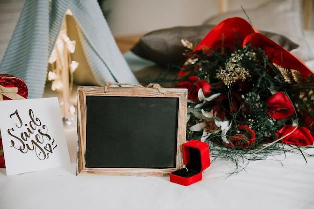 Pierścionek i blackboard blisko bukieta i prezentów