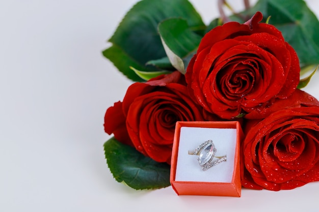 Pierścionek i piękna czerwona róża na białym tle.