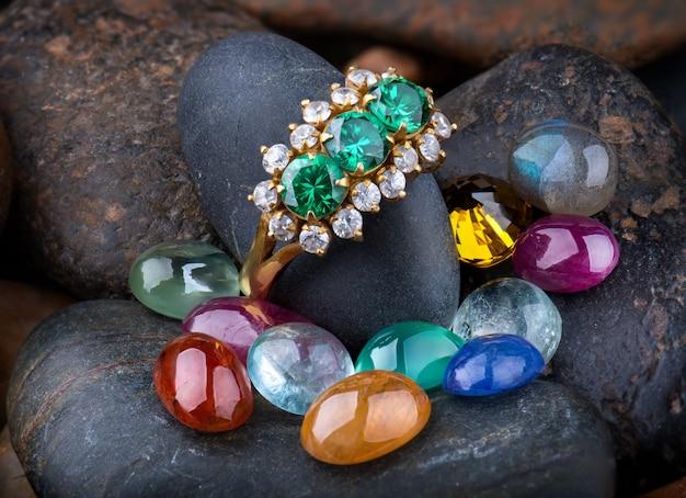 Pierścionek jubilerski i okrągłe kamienie mineralne o szlifie okrągłym.