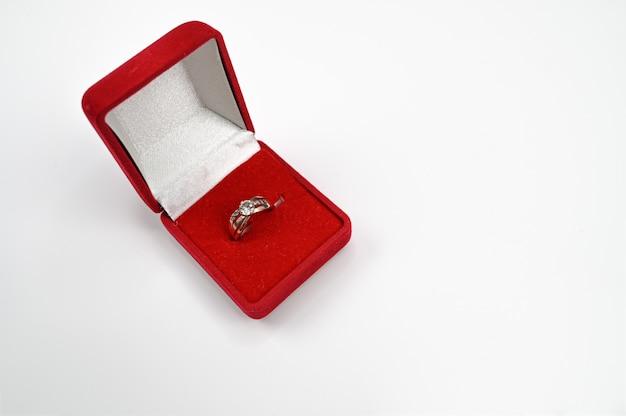 Pierścionek jubilerski z diamentem w czerwonym pudełku.