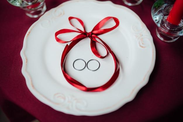 Pierścionek na białym talerzu z kokardą
