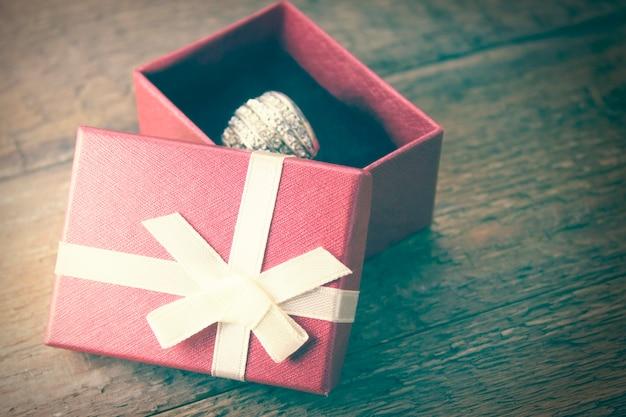Pierścionek na pudełku prezentowym na drewnianym stole