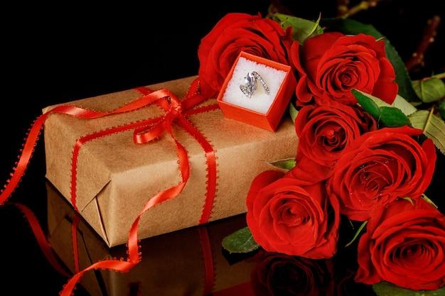 Pierścionek w czerwonym pudełku i piękne czerwone róże na czarnym tle. koncepcja walentynki.