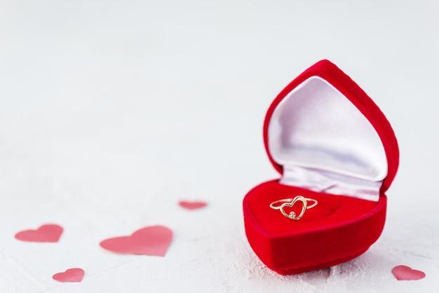 Pierścionek w kształcie serca w pudełku na stole z czerwonymi serduszkami