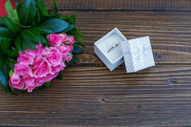 Pierścionek w prezencie i bukiet kwiatów. miejsce na napis