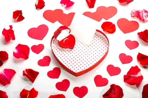 Pierścionek w pudełku w kształcie serca na białej powierzchni z nutą płatków róż w środku
