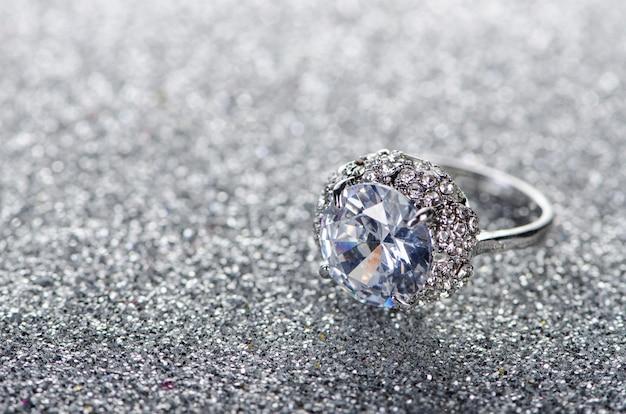 Pierścionek z biżuterią na błyszczącym tle