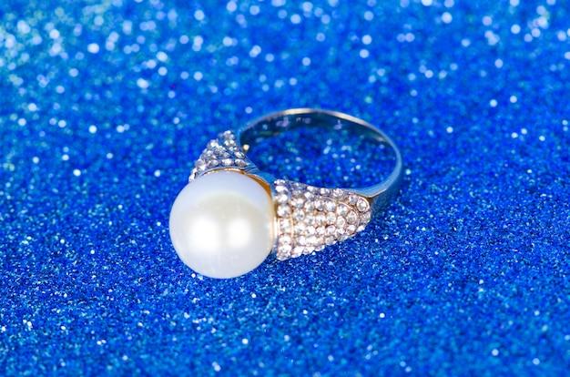 Pierścionek z biżuterią na niebieskim tle
