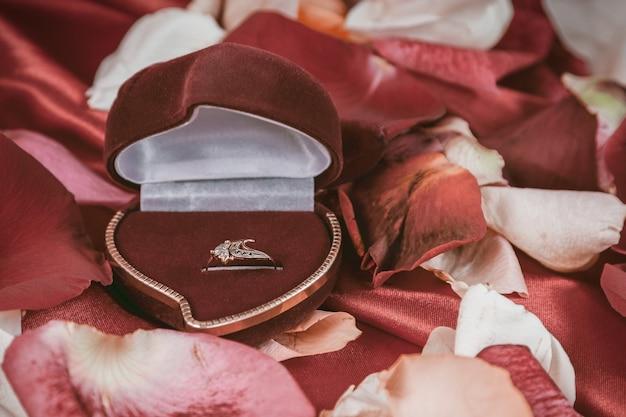 Pierścionek z brylantem i płatki róż na jasnoczerwonym tle