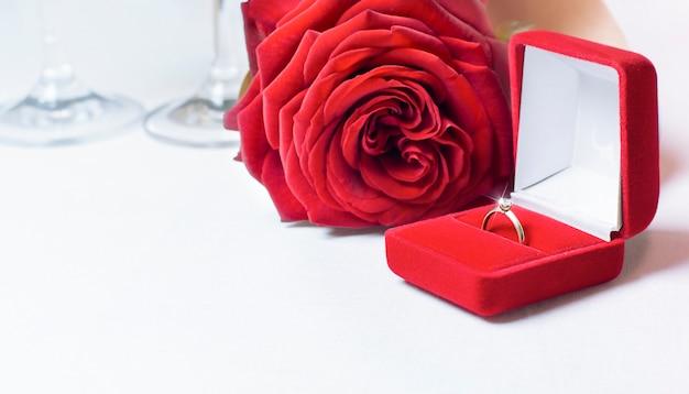 Pierścionek z brylantem i róża na stole