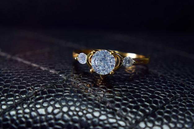 Pierścionek z brylantem, luksusowa obrączka, droga na czarnej skórze