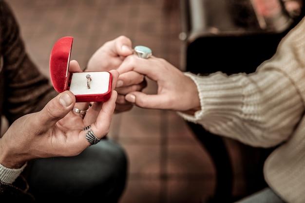 Pierścionek z brylantem. mężczyzna wnosi pierścionek do swojego partnera, składając propozycję