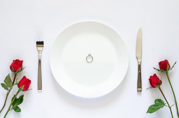 Pierścionek z brylantem stawia na talerz z nożem, widelcem i czerwonymi różami na białym tle dla koncepcji walentynki.