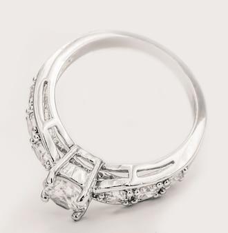 Pierścionek z brylantem z białego złota na białym kremowym tle