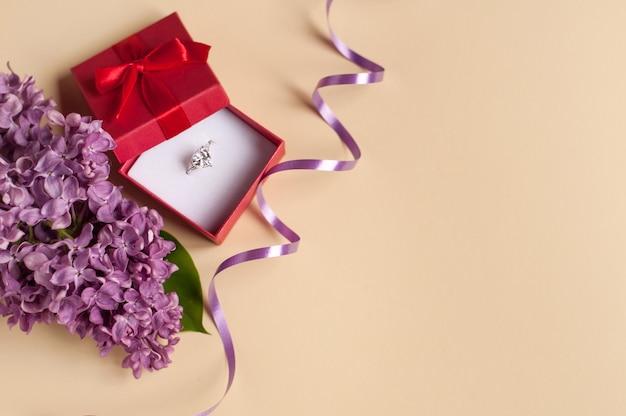Pierścionek z kamieniem w pudełku na liliowym tle