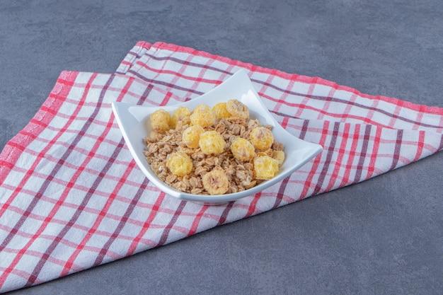 Pierścionek z kukurydzy miodowej z musli w misce na ściereczce, na marmurowym tle.