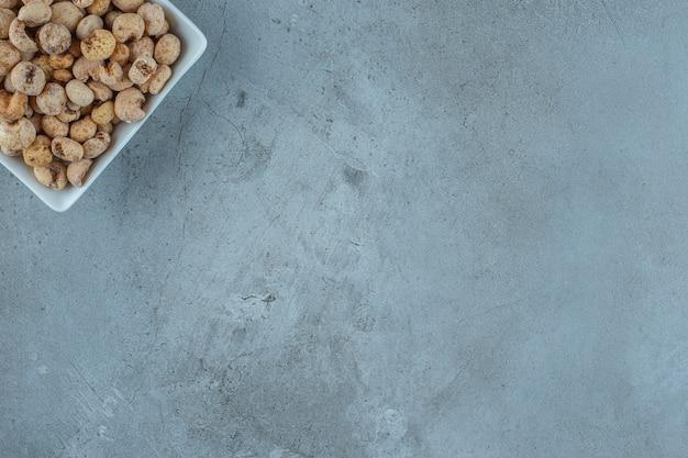 Pierścionek z miodem kukurydzianym z musli w misce, na marmurowym tle.