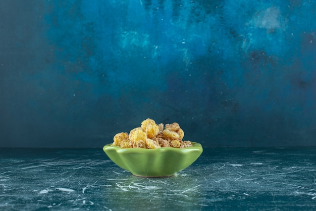 Pierścionek z miodem kukurydzianym z musli w misce, na niebieskim stole.