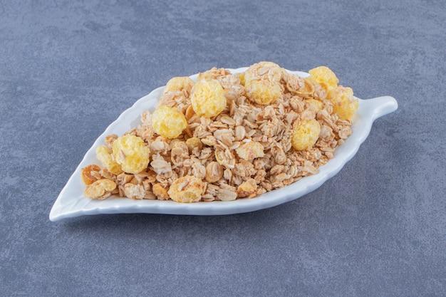 Pierścionek z miodem kukurydzianym z musli w talerzu, na marmurowym stole.