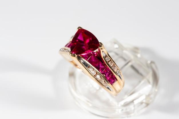 Pierścionek z rubinem otoczony brylantami, o szlifie trylionowym, pierścionek z żółtego złota na stojaku