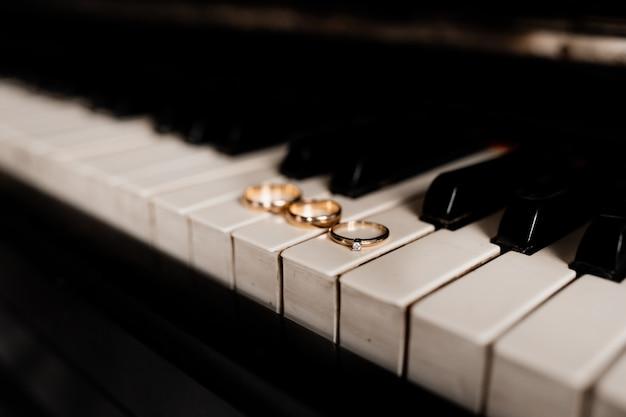 Pierścionek zaręczynowy i para obrączek leżą na klawiszach