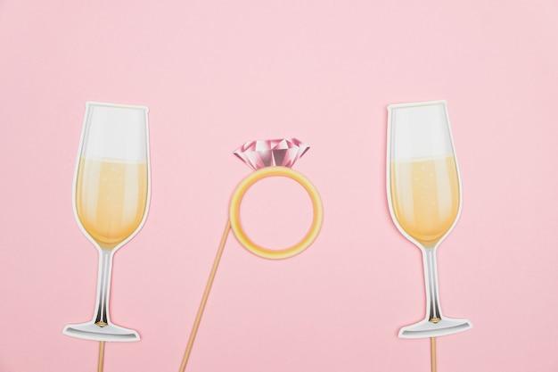 Pierścionek zaręczynowy koncepcja walentynek i kieliszki do szampana z papieru rekwizytu na różowym tle