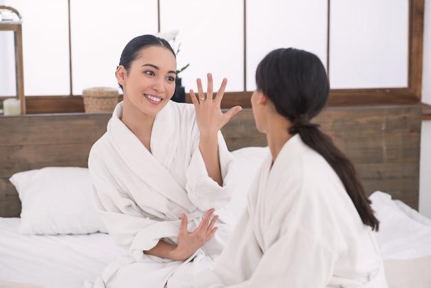 Pierścionek zaręczynowy. przyjemna szczęśliwa kobieta patrząc na swojego przyjaciela, pokazując jej rękę z pierścionkiem zaręczynowym