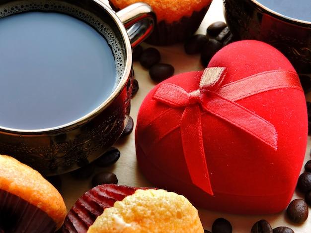 Pierścionek zaręczynowy w czerwonej kopercie, dwie filiżanki kawy i babeczka. koncepcja propozycji małżeństwa. śniadanie na walentynki.