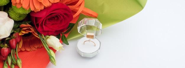 Pierścionek zaręczynowy w pudełku prezentowym z jasnym bukietem kwiatów. oferta zawarcia małżeństwa. prezent na walentynki. propozycja małżeństwa dla ukochanej kobiety. symbol miłości i małżeństwa.