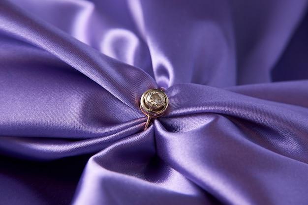 Pierścionek zaręczynowy z brylantem na zielonym tle satyny. złoty pierścionek z brylantem, zbliżenie. luksusowa biżuteria damska, zbliżenie. selektywna ostrość
