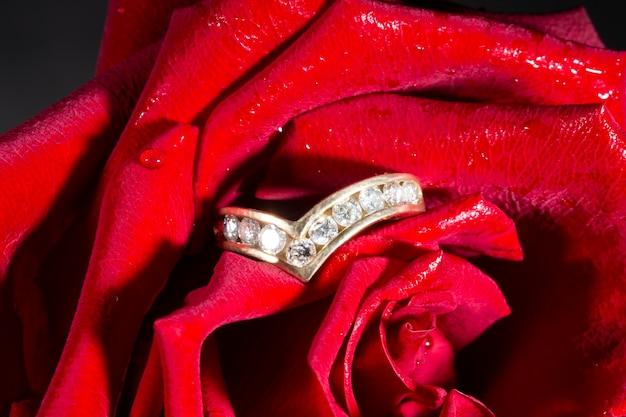 Pierścionek zaręczynowy z brylantem ze ścieżką diamentów i czerwoną różą. koncepcja to propozycja zostania moją żoną