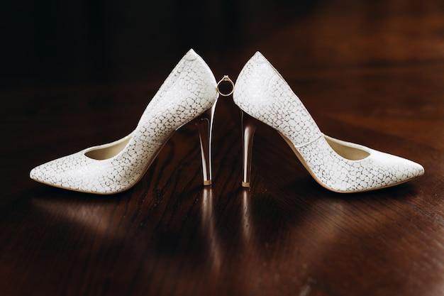 Pierścionek zaręczynowy z kamieniem szlachetnym znajduje się między obcasami ślubnymi