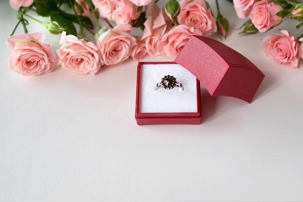 Pierścionek zaręczynowy z klejnotami w otwartym czerwonym pudełku z biżuterią otoczonym jasnoróżowymi różami. obchody walentynek