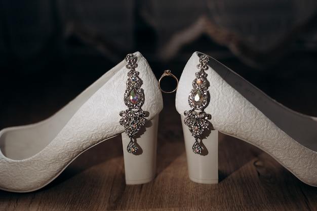 Pierścionek zaręczynowy znajduje się między ozdobionymi obcasami panny młodej