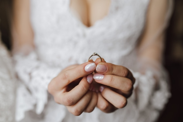 Piersi młodej panny młodej ubranej w suknię ślubną z pierścionkiem zaręczynowym w rękach z diamentem