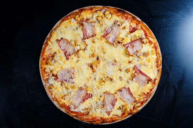Piersi z kurczaka z kremowym sosem i tartym serem na pizzy. smaczna świeża pizza na grubym cieście z mięsem