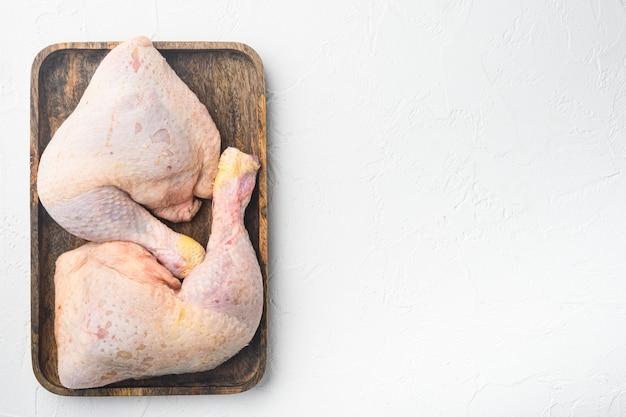 Pierwotne cięcie surowych udek z kurczaka, z udami i podudziami z kurczaka, na drewnianej tacy, na białym kamiennym stole, widok z góry na płasko