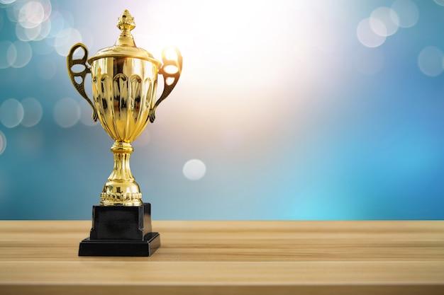 Pierwsza nagroda mistrzowska, najlepsza nagroda i koncepcja zwycięzcy, puchar mistrzowski lub trofeum zwycięzcy na drewnianym stole z miękkim niebieskim i bokeh