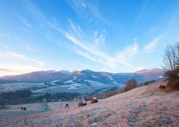 Pierwsze jesienne przymrozki na pastwisku ze stogami siana i wschodem słońca w górskiej wiosce