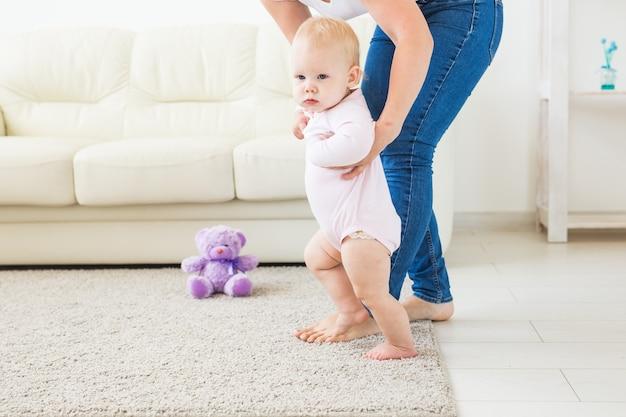 Pierwsze kroki malucha uczącego się chodzić w białym słonecznym salonie. obuwie dla dziecka.