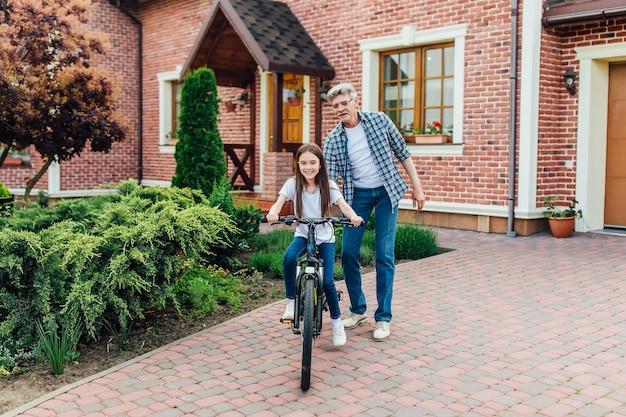 Pierwsze lekcje jazdy na rowerze. przystojny dziadek uczy swoją wnuczkę przeciwko.