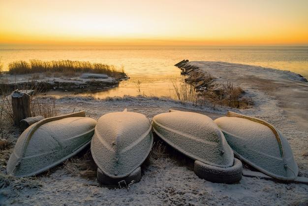 Pierwsze promienie słońca nad jeziorem ładoga rano zimą. wywrócone łodzie na śnieżnej plaży. obwód leningradzki .panorama.