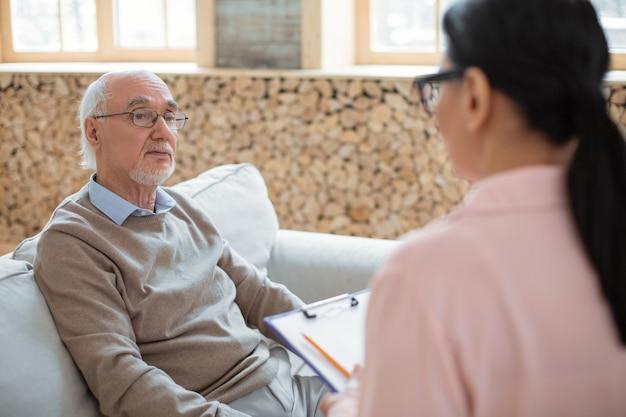 Pierwsze wrażenie. uroczy przystojny starszy mężczyzna siedzi na kanapie, patrząc na opiekuna i komunikując się z nią