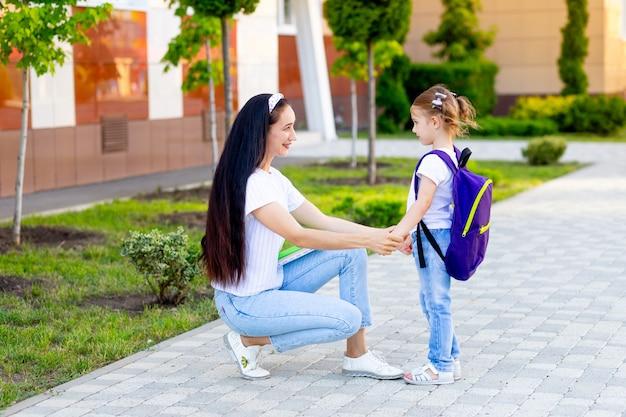 Pierwszego dnia szkoły matka prowadzi małą uczennicę do pierwszej klasy trzymając się za ręce, koncepcja wraca do szkoły