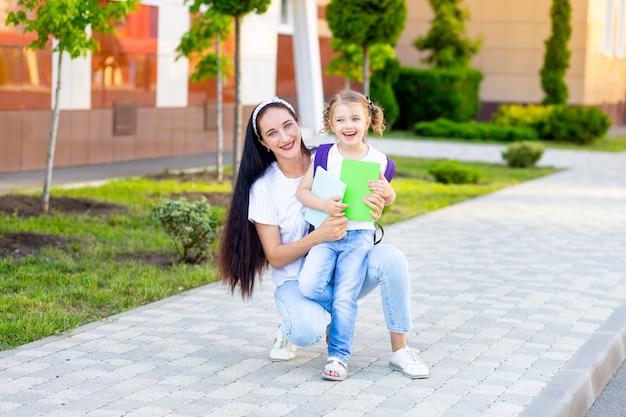 Pierwszego dnia szkoły matka rodzica prowadzi uczennicę do pierwszej klasy, koncepcja wraca do szkoły